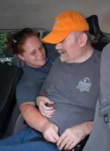 Care Giver Buckling Patient into Van